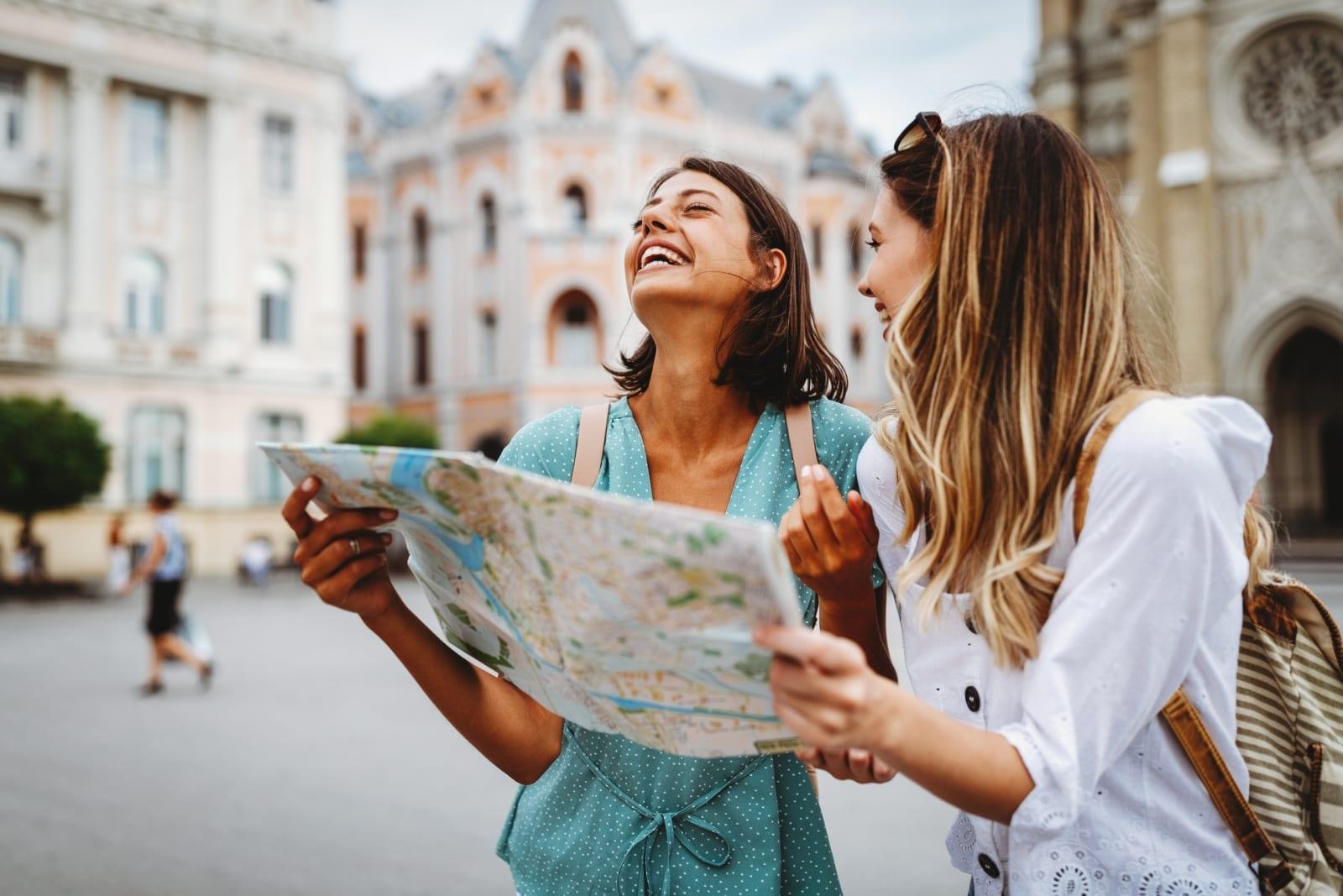 Ragazze che visitano la città e ridono guardando una mappa della città